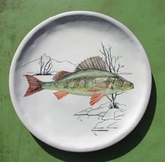 """""""Perca"""". Perteneciente a la serie  peces de río. 26 cm. de diámetro. Plato artesano pinado a mano. Técnica sobre cubierta/ barro rojo."""