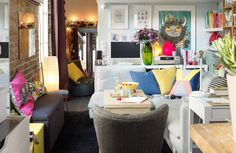 View of living room. Neutral colored walls and sofa are brightened with colorful textiles, art work, books and storage.