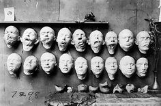 Masks showing the work done by Anna Coleman Ladd of the American Red Cross. Casts on the top row were taken of soldiers' mutilated faces; the bottom row shows masks of their faces before their injuries that were made from pre-war photographs. On the table are masks made to fit over the disfigured part of the face. 1918.