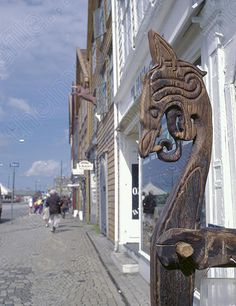 Traditional dragon's head carving, Bryggen, Bergen, Hordaland, Norway.   Keywords: Norwegian Hanseatic quayside wooden wood timber warehouses picturesque pretty beautiful historic Scandinavian old medieval ancient bright sunny summer day blue sky waterfront lgpl