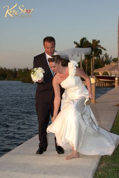 The groom helping his bride while she is taking her shoes off. After all...we are in the Keys!