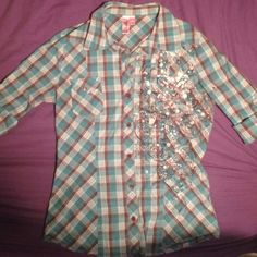 Plaid button up cowgirl shirt Teal and brown plaid shirt with brown, silver, and white design on the left side. The size says Large but it fits like a medium. Material is stretchy (3% spandex). The sleeves roll up and secured with a button. This is a reposh because it did not fit. perfect condition! Dolled Up Tops Button Down Shirts