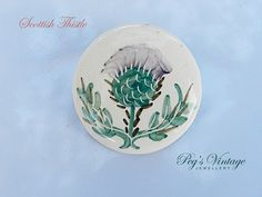 1960s ceramic glazed round thistle pin  Unique Vintage round ceramic brooch featuring painted Scottish thistle design. Leaves are green, and