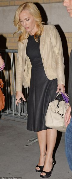 Home time: Anderson topped her demure look with a sparkly gold blazer as she toted a match...