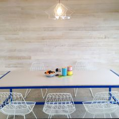 Simple, scandinavian style featuring a timber clad wall, powder coated steel frame table with plywood top, bent wire chairs, acrylic laser cut light and a splash of colour x  Table by Hard Art Co Light by Luum Chairs from Bunnings