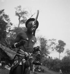 Part of the Nkporo Ifogu masquerade.An Mba dancer performing in the Ifogu masquerade, wearing an Ogu mask, an abstract wooden face mask with a knife-like protrusion from the forehead, three cylindrical protrusions and slits for the eyes). G. I. Jones, 1930s