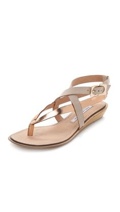 Diane von Furstenberg Dottie Wedge Sandals  Two-tone straps in smooth and metallic leather contour a stylishly secure fit for chic DVF sandals. A delicate wood wedge subtly lifts the silhouette. Adjustable ankle strap and leather sole.