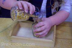 Pour popcorn seeds from one jar to another. Go to water and/or sand next.