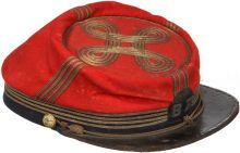 """Zouave"" Style Chasseurs Officer's Kepi. It features four bands of narrow gold braid that surround the cap's dark blue wool band and proceed up the front, back, and sides. The crown is bordered by one band of the same braid and four more bands that loop into a quatrefoil in the center. A narrow braided gold cord chinstrap is attached by two staff officer side buttons and the cap is complete with a thick glazed visor. Sewn on the front is a patch of blue wool with the embroidered letters…"