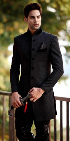 Aristocratic Black Indo Western Sherwani - Attract to everyone with your ethnic charm in this black shade indo western sherwani, features rich self woven decorative patterns all over. Amazing velvet collar, decorative buttons on front panel is beautifully enhance the look. Paired with a matching breeches (it's a fusion of modern style baggy trouser) churidar.