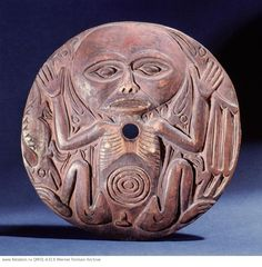 Salish. Spindle whorls were used by the Coast Salish during spinning to prevent the wool slipping from the spindle. This spindle whorl is decorated with a human figure in a foetal position, a common motif in NWC design. Birds and an otter surround the figure and may represent spirit helpers of the weaver. Country of Origin: Northwest Coast of America. Culture: Salish. Date/Period: collected 1884. Place of Origin: Cowichan, Vancouver Island. Material Size: wood.