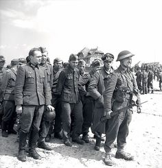 WWII- A Canadian soldier stands at the head of a group of prisoners, including 2 officers at the front, who surrendered in Courseulles-sur-Mer, Normandy, on D-Day, June 6, 1944. [Image Credit; PD] AHC/ qw