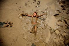 A boy plays in the mud on the bank of the Bago river in Bago
