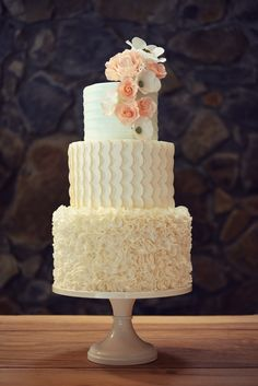 Three tiered wedding cake with white bunched ruffles, white scallops, and a faintly mint accent tier with white stripes, adorned with sugar flowers in whites and pinks www.countrycakeshop.com