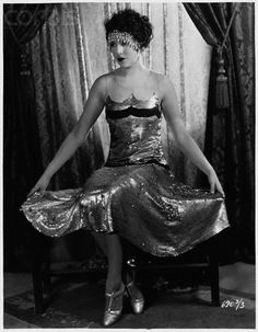 Actress Bebe Daniels in Sequined Dress  Bebe Daniels models a dress decorated with silver sequins and wears an elaborate headband of drop crystals.  Date Photographed: ca. 1920s
