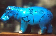Hippo in blue Egyptian faience    The hippopotamus (no longer found in Egypt) was a danger to boats on the river Nile, and to people working on or near the river banks. These animals were represented by the goddess Tauret, and offerings were made to her in the hope of placating her. She was also a goddess of fertility, represented as a pregnant hippopotamus.    Many models of hippopotami were made of blue Egyptian faience, their bodies decorated with representations of the river plants that…