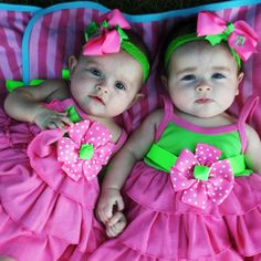 Cute little twins in pink and green outfits.