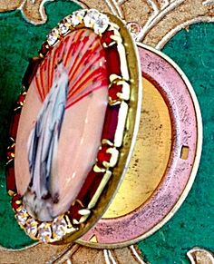 $88 Prayer petition porcelain cameo locket featuring the Blessed Mother Virgin Mary as Our Lady of Grace and Miracles. The cameo is surrounded by baguette and round deep Red rhinestones and clear rhinestones. Inside is copper and brass and can hold 2 photo's and/or your personal prayer petition request to Mary.