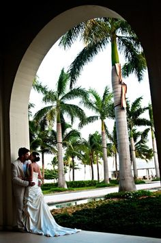 Her dress is so elegant. The brides dress likes to flow to the floor while the arch is so dramatic its all about cemetery!       Make your dream wedding come true:                     1-866-383-6810 #dreamwedding #keywestwedding #dayofwedding #weddingplannerkeywest #planmywedding #wedding #fantasywedding #beachwedding