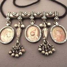A splendid old amulet coming from Rajasthan (INDIA) with 3 portraits of three men of importance dating probably from early 20th century ...in between 2 pendents in form of fish with small grelots up a