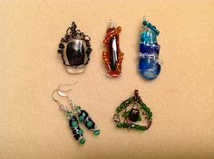 Wire and fused glass pendants and earrings.  The shapes of the glass starts out one way and may change during fusing...the earrings had the little balls straight when started......fused off center....but they turned out cool.