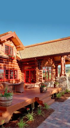 Beautiful log home with red trim and a perfect porch.