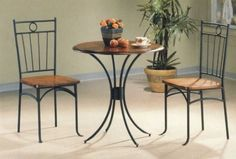Three piece bistro dining set features gentle curves of the metal pedestal base that compliment the round wooden table top that is bathed in a warm finish. The two side chairs mirror the bistro table with wooden seats and a unique metal seat back. #BistroTables #3pc #Table
