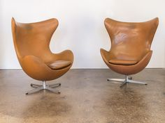 "An exceptional pair of vintage cognac leather Egg chairs by Arne Jacobsen for Fritz Hansen. Sculpted backs command attention while also cradling the body comfortably within it's curvilinear form. From the early 60s, the twenty-five year leather is soft and nicely broken-in maintaining an attractive patina. Foil labels and stamps present on the aluminum four star swivel base. These iconic, modern lounge chairs can not disappoint.  35"" wide x 22"" long x 42"" high x 16"" seat height  6L2V5XK59V"