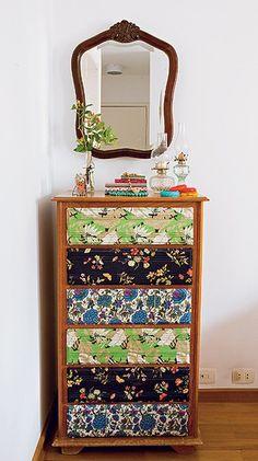A cômoda tem gavetas revestidas de tecidos de roupas antigas, invenção da ilustradora Cynthia Gyuru. Uma opção sustentável e barata