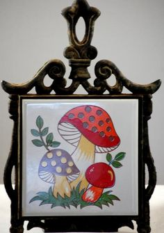 This is a vintage 1970s black cast metal and mushroom tile trivet. The trivet is 12 inches high and 7 and 1/2 inches across. The tile is marked Japan and features a colorful groovy hippie mushroom design. The trivet has the orig...
