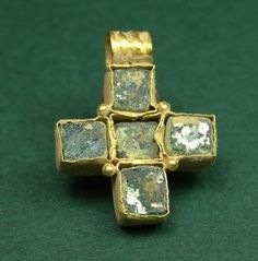Byzantine gold and glass cross pendant, 400-600 AD. With four inset blue square shaped glass stones, supported with four gold granules on the sides.