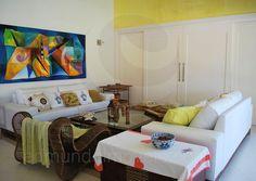 No térreo, a ampla sala para 4 ambientes integra espaços flexíveis e mobiliados com modernidade, coordenando a descontração com as cores vivas presentes nas almofadas, nos quadros e nas paredes.