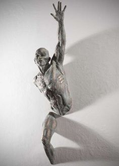 The sculptures of Matteo Pugliese are cemented into the wall and look as if they're trying to break free.