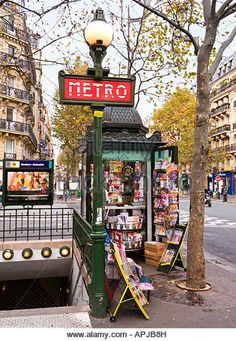 Paris Metro sign Metro entrance on the Boulevard Saint-Germain and typical small French newsagent kiosk, Paris, - Stock Image