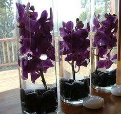 Centrepieces - like the cylinder glass vases with the black stones but would have red carnations & bear grass