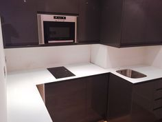 This sleek and stylish white worktop lends light  and a sense of elegance to this compact Kensington studio