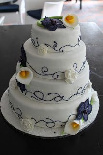 Purple and white wedding cake with cala lilies and orchids