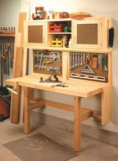 This workstation has it all — a space-saving, fold-down workbench, easy-access tool rack, and plenty of storage in a wall-mounted cabinet. Workbench Plans Diy, Folding Workbench, Woodworking Workbench, Woodworking Shop, Woodworking Crafts, Garage Workbench, Woodworking Basics, Desk Plans, Workbench Stool