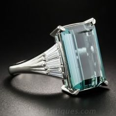 A gorgeous Art Deco inspired estate cocktail ring featuring a rather enchanting gemstone. An emerald-cut tourmaline, weighing 11.35 carats, imbued with an exotic bright greenish-blue hue, elegantly fashioned with a striking vertical faceting arrangement, glistens and glows between sparkling fans of bright white tapered baguette diamonds totaling .60 carat. Hand-fabricated in platinum. Late 20th century vintage, and beautifully bargain priced. 3/4 by 1/2 inch. Currently size 8 1/4.