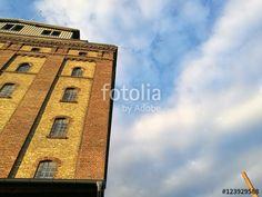 Alter Getreidespeicher im Licht der Abendsonne und alter Fabrikschornstein vor blauem Himmel mit Wolken am Hafen von Münster in Westfalen im Münsterland