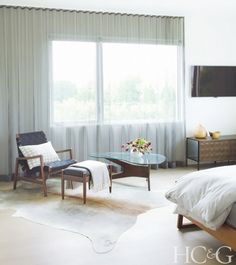 Cozy bedroom with a gray floor to ceiling sheer curtain, a cowhide rug, and a midcentury modern armchair
