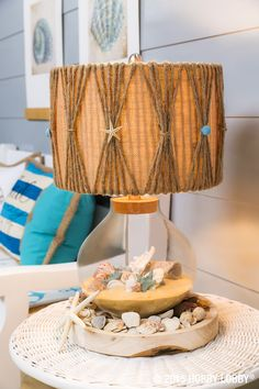 Making a seashell lamp is a breeze! 1. Wrap jute around lampshade, allowing 6 pieces to be gathered for each section. Tie gathered pieces with jute. 2. Glue a seashell or starfish to the area where the jute was gathered.  3. Fill bottom of lamp with sand and seashells.