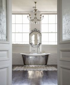 Silver & white scheme. Gorgeous silver bath. Love the way mirror, chandelier & bath all in a line