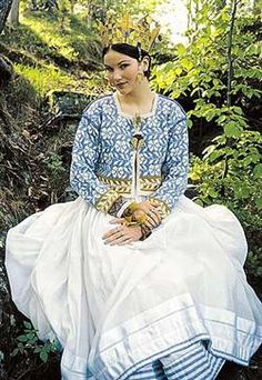 The designer of this bridal jacket, Solvejg Hisdal, was inspired by seeing a pale blue and white silk chest cloth from Hardanger Folkemuseum. The chest cloth is decorated in velvet ribbons, glass beads, gold thread and silver thread. Pale blue and white is used for the main pattern, while the golden touch is expressed in the beaded border at the edge of the sleeves.