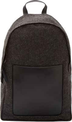 "Backpack in charcoal grey felted wool. Black leather front pocket, top handle, base panel, and trim. Adjustable shoulder straps in olive. Concealed zip-around closure at main compartment with logo-embossed leather pull tabs. Interior pockets. Fully lined in black textile. Tonal stitching. <br><br> Measures approx. 12"" length x 16"" height x 6"" width."