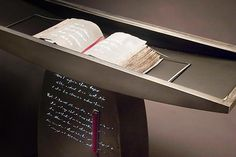 Written Word Table by Ken Girardini and Julie Girardini. Steel and Glass Table with a sculptural handmade book under glass (glass top not shown). The book is made of Kozo paper and has images of hand written text on the sheets. The steel below the book is also pierced with the text and light shines from inside to project the words onto the open pages of the book. The base has light projecting from the open lettering. A leather bound red journal is part of this one of a kind art piece to…