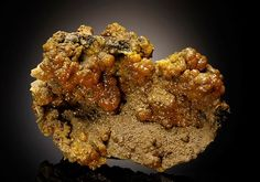 Classic botryoidal crystalline orange to yellow-orange Pyromorphite lines a deep to shallow cavity on Quartz and 'Limonite' cemented by Pyromorphite. From the Bunker Hill Mine, Kellogg, Idaho, USA.