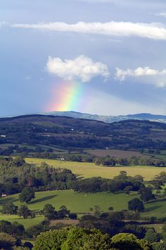 Clwydian Hills, North Wales, UK wide rainbow reaching from white clouds in sky to mountains tops,