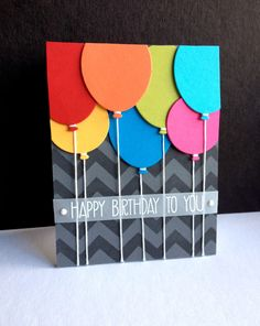 handmade birthday card from Im in Haven ... Penny Black balloon died cut in bright colors with string hanging down ... luv that she made her own chevron stencil using a die cut and acetate for the gray on gray background ... white embossed sentiment on vellum belly band ... great card!