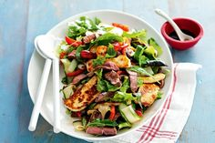 Lamb, Haloumi & Roasted Capsicum Salad ----   2 Red Capsicum -      2 tbs Olive Oil ---      400g Lamb Leg Steaks, trimmed - med high, 3 min each side, rest 5 min covered, thinly slice ---     180g Haloumi Cheese, thickly sliced - pan fry 1-2 min each side ---     2 Lebanese Cucumbers, cut into thin ribbons     60g mixed Salad Leaves     2 tbs Balsamic Vinegar